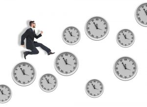 Geeky young businessman running mid air against clocks